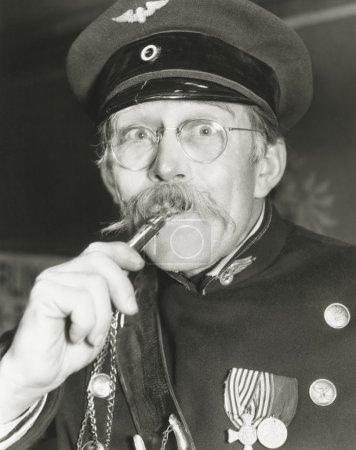 Senior man blowing whistle