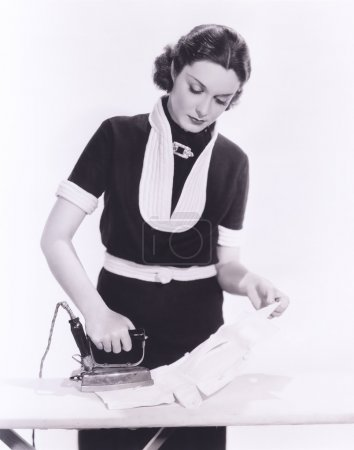 Photo for Woman ironing clothes at home - Royalty Free Image