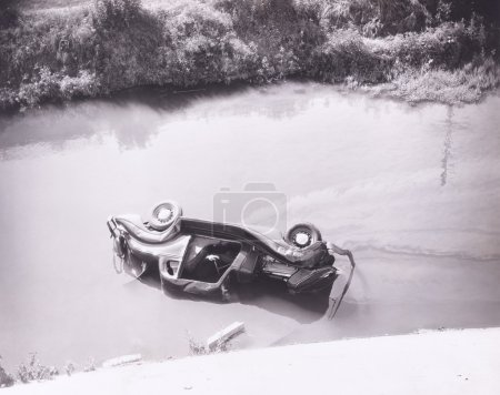 Photo for Person trapped in overturned car in swamp - Royalty Free Image