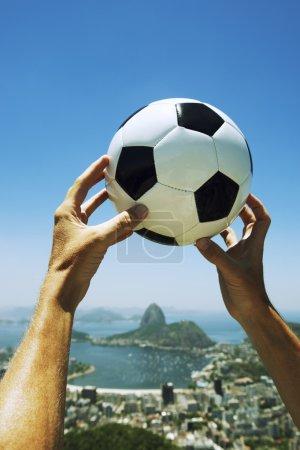 Hands Holding Football Soccer Ball Above Rio de Janeiro Brazil