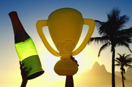 Photo pour Célébration des mains retenant le trophée gonflable et la bouteille de champagne au-dessus de l'horizon de coucher du soleil de Rio de Janeiro Brésil - image libre de droit