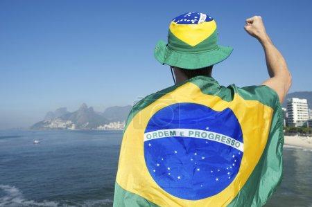 Brazilian Man Pumping Fist with Flag Rio Skyline