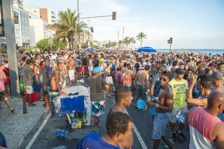 Photo pour Des foules de Brésiliens célèbrent lors d'une fête de rue au coucher du soleil le long de la plage d'Ipanema à Rio de Janeiro, Brésil . - image libre de droit