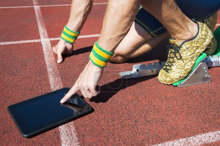 Photo for Athlete in gold running shoes crouching at the starting line of a running track wearing Brazil colors wristbands using his tablet - Royalty Free Image