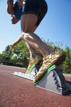 Photo for Athlete in gold shoes starting a race from the starting blocks on a red running track - Royalty Free Image