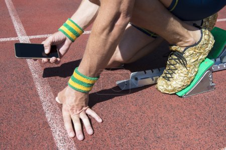 Photo for Athlete crouching at the starting line of a running track wearing Brazil colors wristbands checking his mobile phone - Royalty Free Image