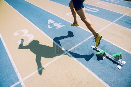 Photo for Athlete in gold shoes sprinting from the starting blocks over the starting line of a race on a blue and tan running track - Royalty Free Image