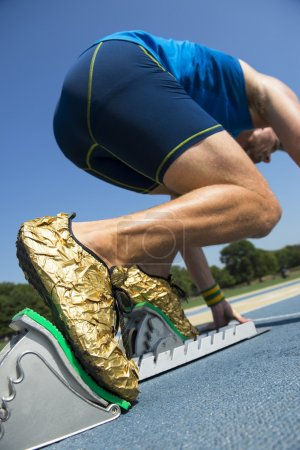 Photo for Athlete in gold shoes starting a race from the starting blocks on a blue running track - Royalty Free Image