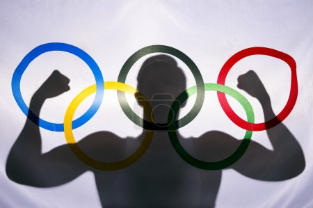 Silhouette of Athlete Behind Olympic Flag