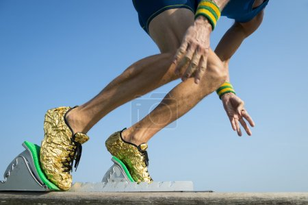 Photo for Athlete wearing gold running shoes takes off in a blur from from the race track starting blocks - Royalty Free Image