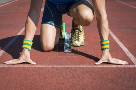 Photo for Athlete crouching at the starting line of a running track with gold shoe feet in sprinter starting blocks - Royalty Free Image