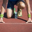 Athlete crouching at the starting line of a runnin...