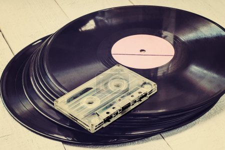 Old vinyl records and audio cassette. Toned photo