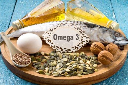 Photo pour Produits - source des acides gras oméga 3 (maquereau, huile de caméline, huile de colza, œufs bio, graines de citrouille et de lin, noix) sur une planche de bois ronde - image libre de droit