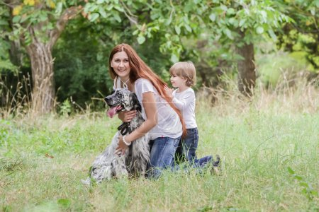 Young mother with toddler and dog enjoying their time on nature,