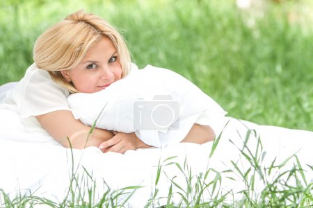 outdoor portrait of young happy woman relaxing on natural backgr