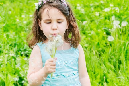 Beautiful child girl with dandelion flower in spring park. Happy