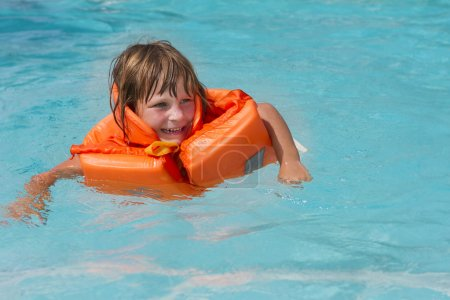 young happy smiling child girl in inflatable life-jacket swimmin