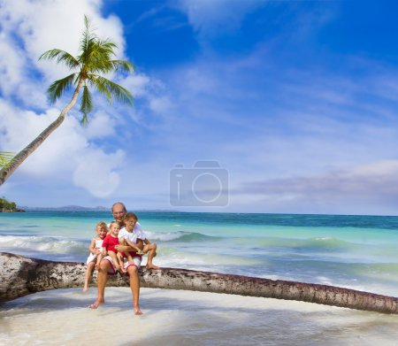 Happy smiling family father and three kids on tropical beach and