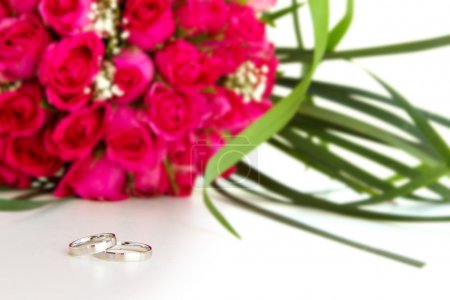 wedding rings and bridal bouquet of pink roses isolated over whi