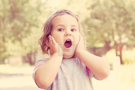 outdoor portrait of surprised cute child girl on natural backgro