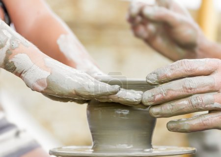 Photo pour Enfant apprendre à faire un pot sur une roue de poterie, vieux potier aide - image libre de droit