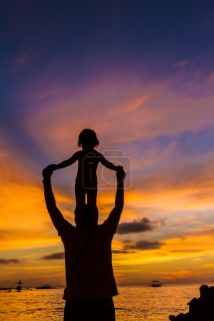 Silhouettes of father and child on sunset sea background