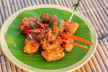 Photo pour Poulet frit à la sauce au miel, boulette de viande servie sur feuille de palmier - image libre de droit