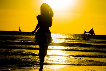 carefree woman dancing in the sunset on the beach. vacation vita