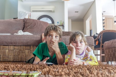 two young children watching tv at home