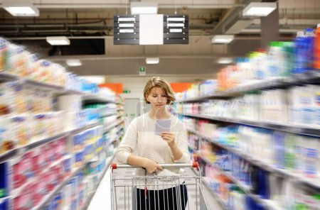 woman with shopping list pushing cart looking at goods in supermarket