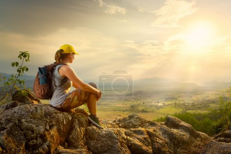 woman with backpacker sitting on top of the mountain and enjoyin