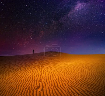A backpacker is walking among sandy dunes under the starry sky