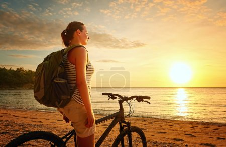 Traveler girl with backpack enjoying view of beautiful sunset.