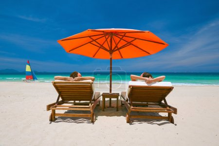 Couple on a tropical beach on deck chairs under a red umbrella