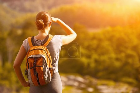 Young tourist with a backpack enjoy the beautiful view. Camera f