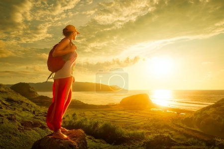 Woman hiker standing on the top and enjoying sunset over sea.
