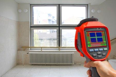 Photo pour Radiateur enregistreur de chauffage et une fenêtre sur un bâtiment à l'aide de la caméra thermique infrarouge - image libre de droit