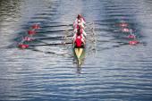 Eight men rowing