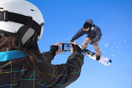 Photographed snowboarder jump with cell phone