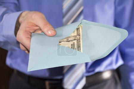 Photo pour Homme dans une chemise bleue, donnant le pot-de-vin dans une enveloppe bleue - image libre de droit