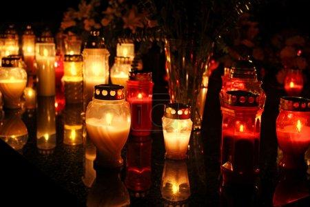 Photo pour Beaucoup de bougies brûlant à un cimetière pendant la Toussaint - image libre de droit