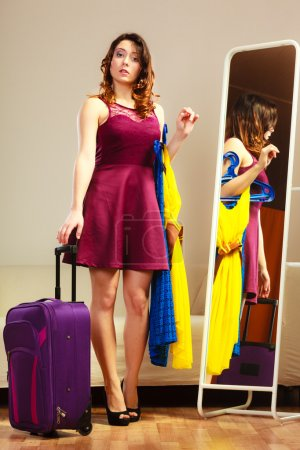Girl holding suitcase at home