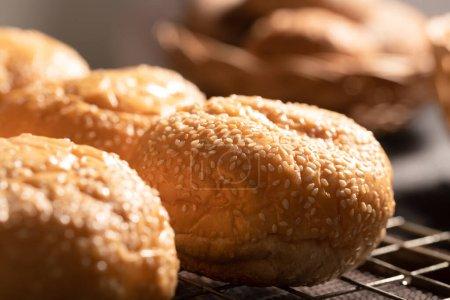 Photo pour Gros plan petits pains sur la grille de la cuisine avec lumière du soleil le matin. Grouper le pain sur la table. Concentration sélective. - image libre de droit