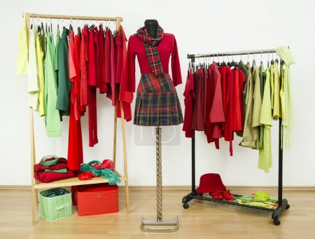Dressing closet with complementary colors red and green clothes arranged on hangers and a plaid outfit on a mannequin.