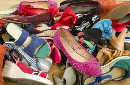Close up on big pile of colorful woman shoes.
