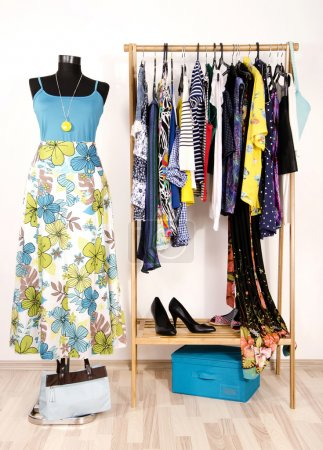 Dressing closet with colorful clothes arranged on hangers and a