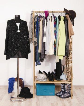 Foto de Armario vestidor con ropa de otoño y accesorios. Sastre 's maniquí vestida con un jersey de lentejuelas y falda negra. - Imagen libre de derechos