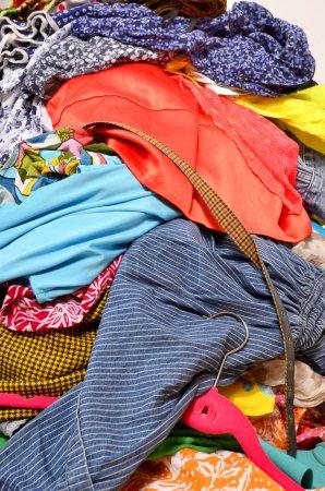Photo pour Armoire désordonnée encombrée avec des vêtements et accessoires colorés . - image libre de droit