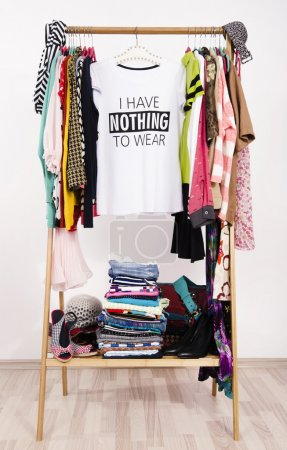 Photo for Close up on a cluttered wardrobe with colorful clothes and accessories, many clothes and nothing to wear. - Royalty Free Image